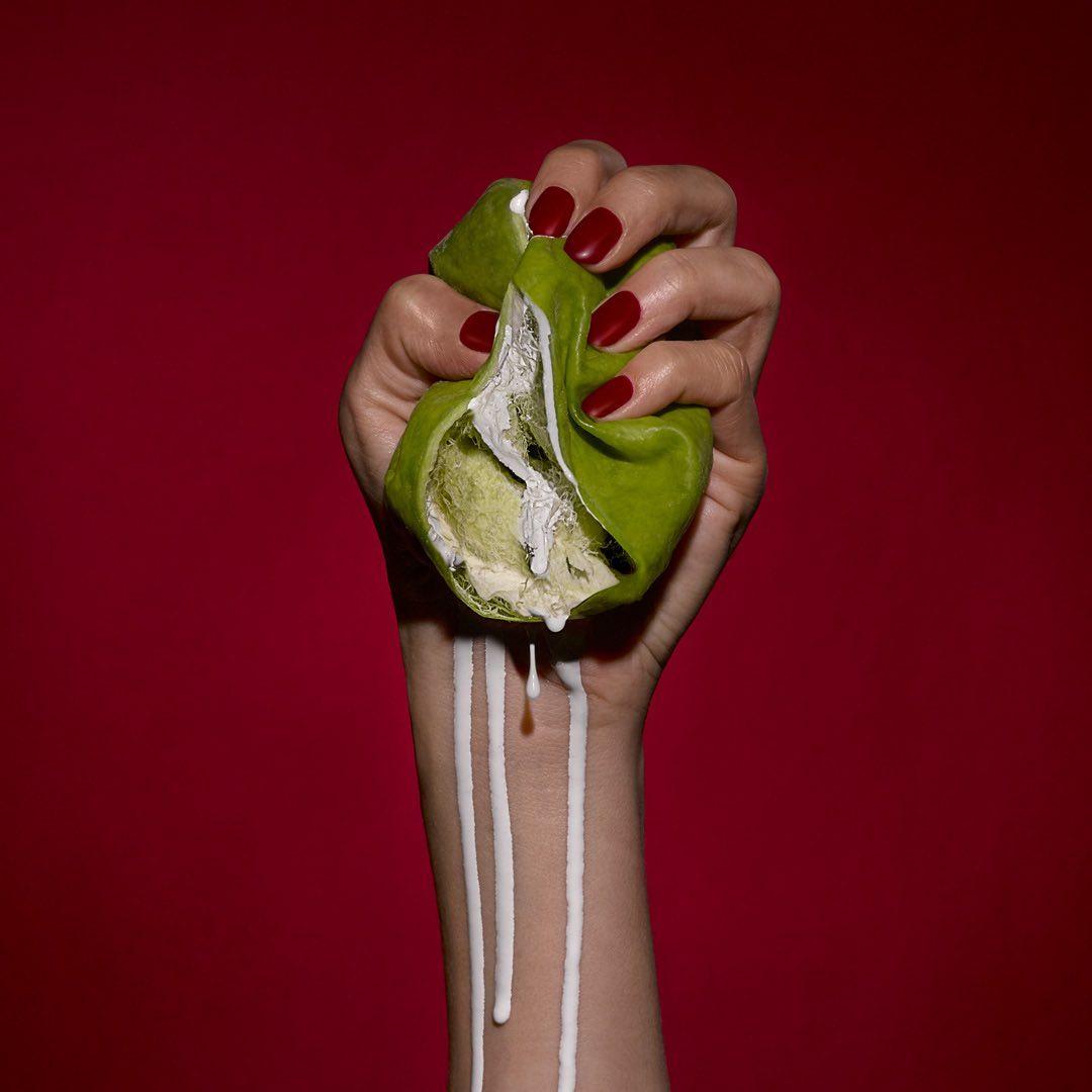 Mano sostiene una manzana aplastándola