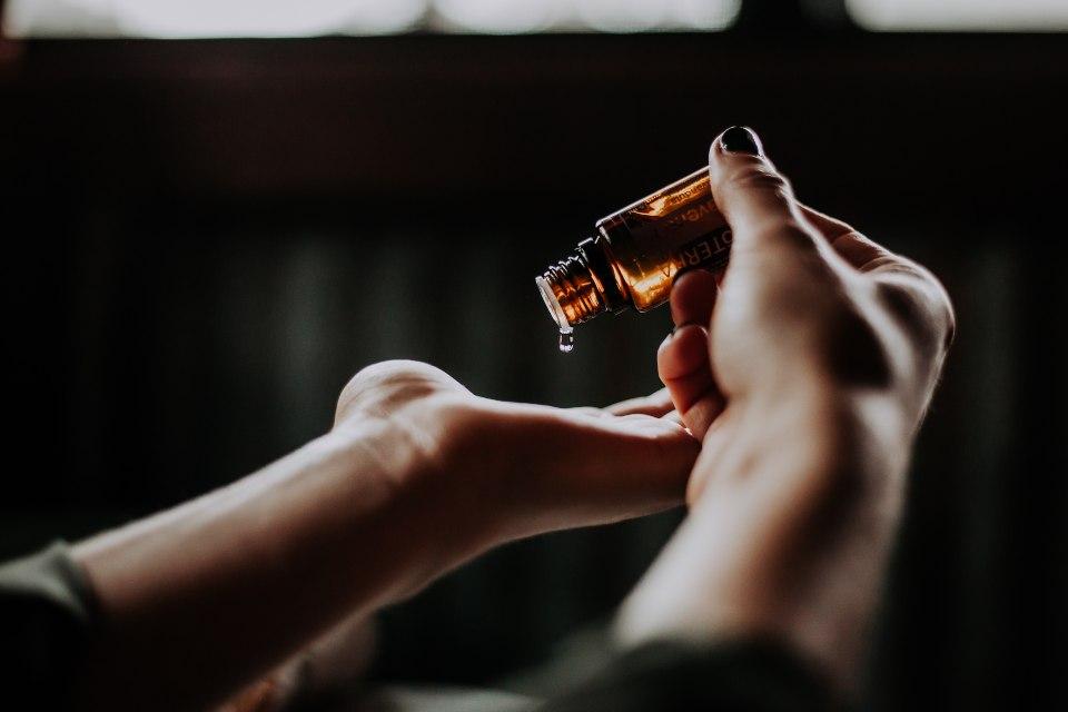 Manos femeninas aplicándose aceite en la piel