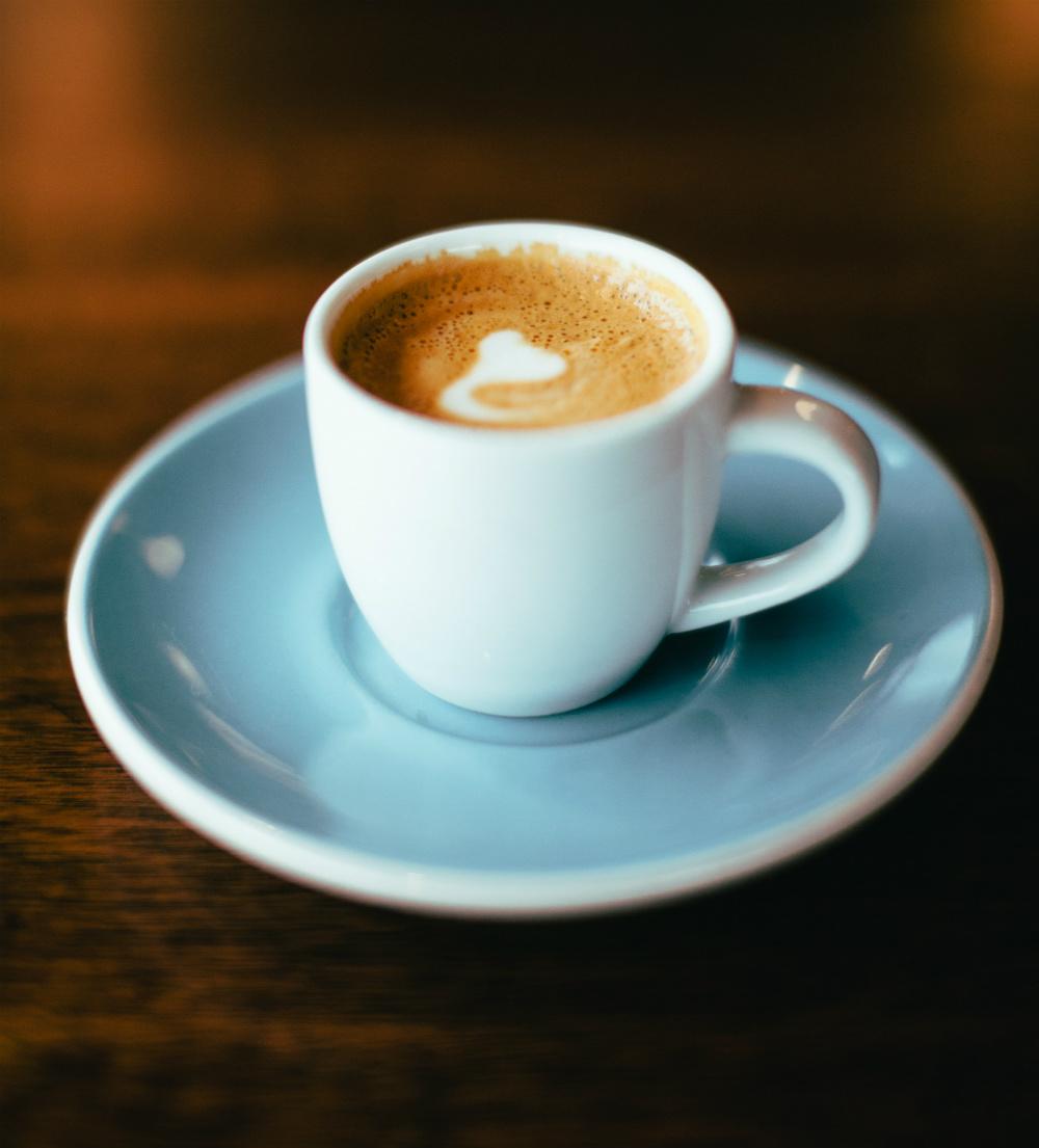 Foto de taza de café oscuro recién servido con espuma en una taza azul.