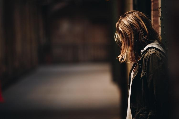 Chica con depresión se recarga en la pared mientras ve con tristeza hacia un lado.