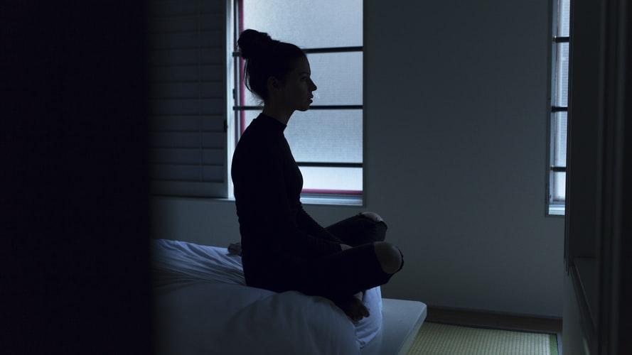 Chica ve hacia el infinito con tristeza mientras se sienta en la orilla de la cama.