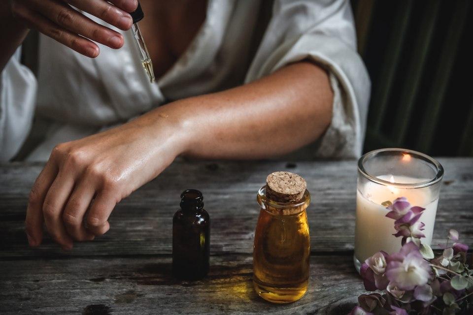 Mujer poniéndose unas gotas de aceite en la piel