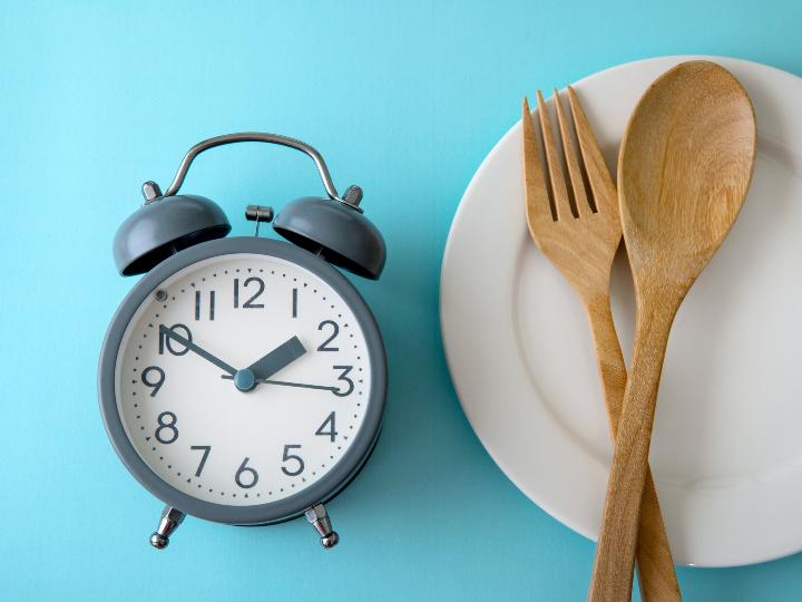 Imagen ilustrativa: reloj con cubiertos y plato de madera.