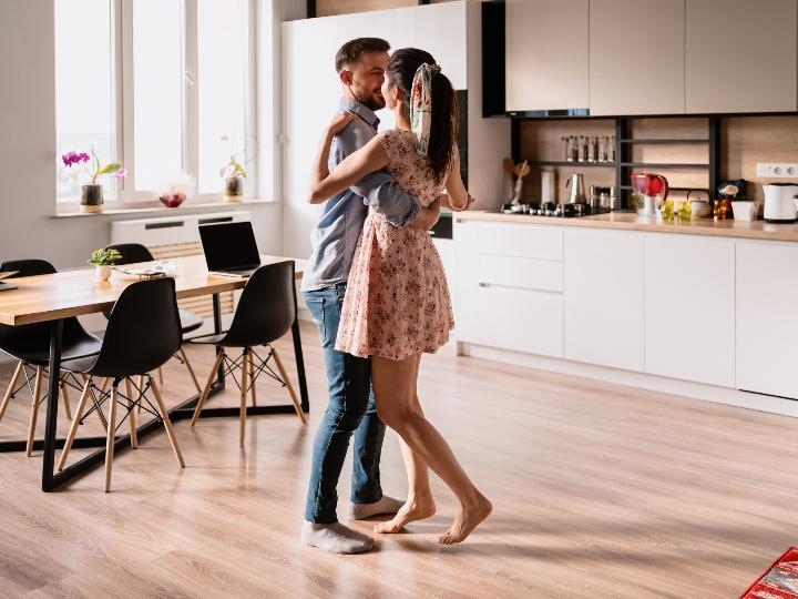 Imagen ilustrativa: mujer bailando con su pareja en un departamento.