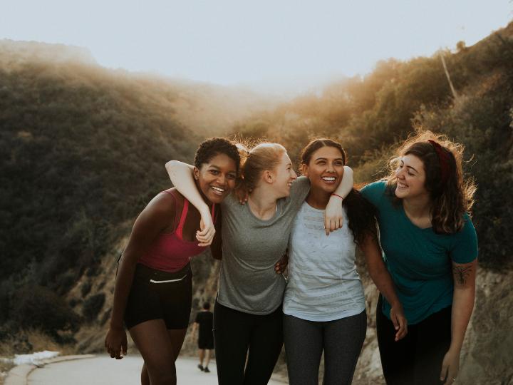 Imagen ilustrativa: grupo de mujeres terminando de ejercitarse caminan juntas mientras ríen.