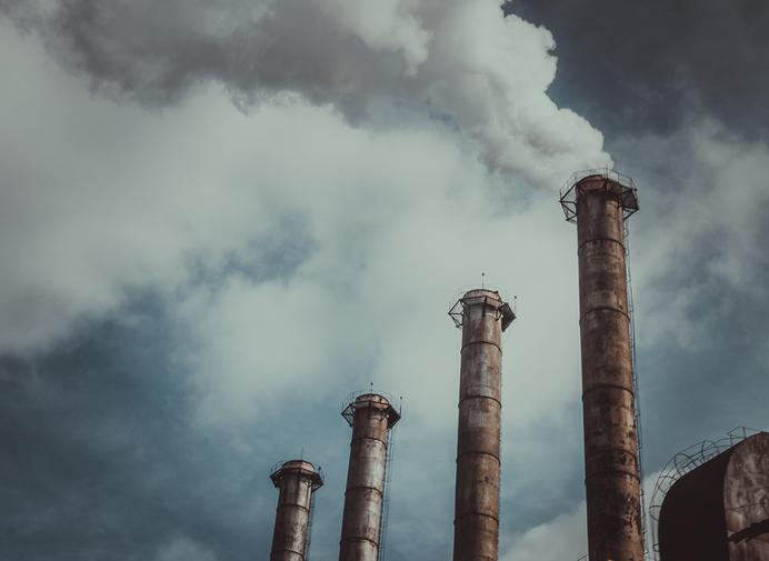 Chimeneas de fábricas lanzando humo contaminante al aire.