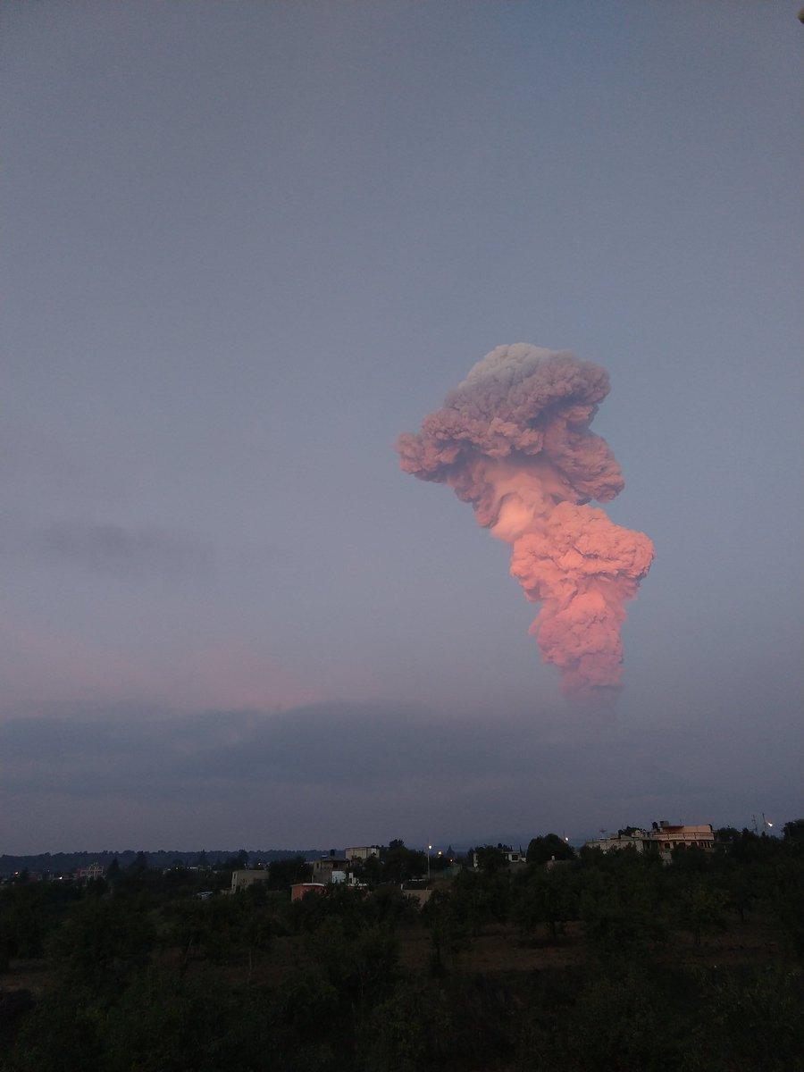 Imagen de la enorme fumarola en tonos rojizos por el reflejo de la luz del amanerce