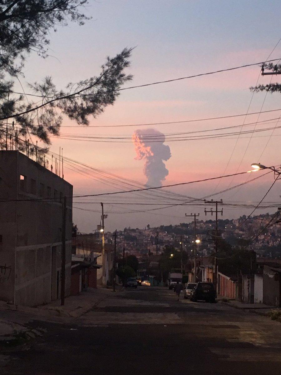 Fotografía de una calle empinada en la que al fondo puede verse una alta columna de humo que nace del Popocatépetl iluminada por los rayos del sol