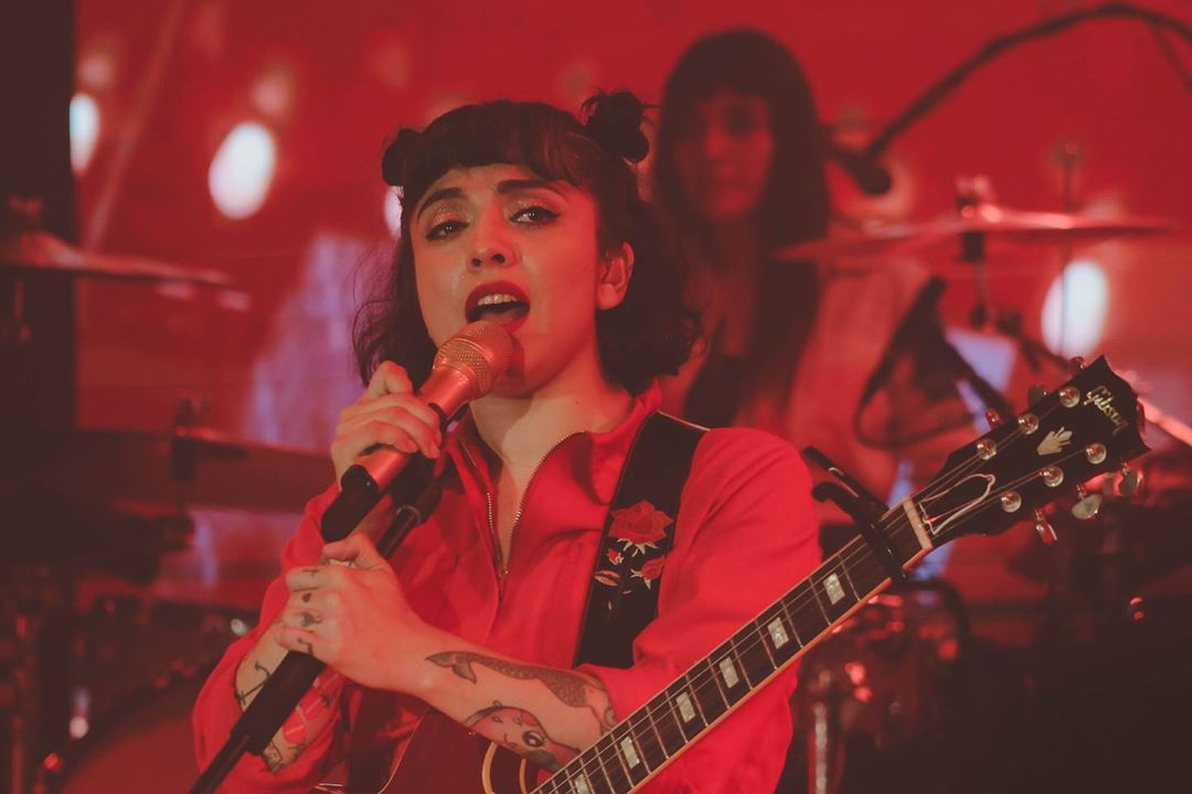 Mon Laferte vestida de rojo cantando con su guitarra colgada al cuello.