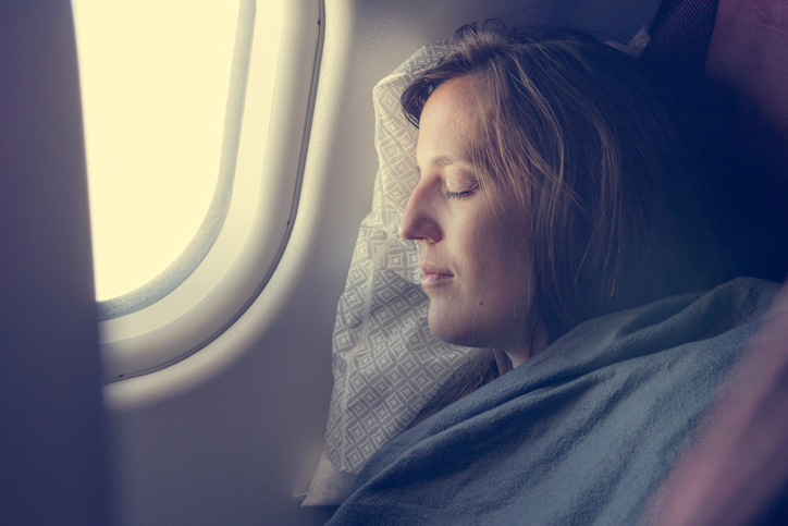 Foto de una mujer dormida junto a la ventanilla de un avión