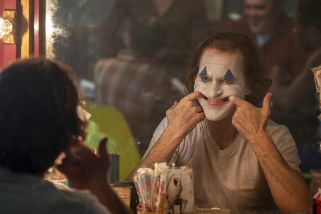 Joaquin Phoenix abriéndose una sonrisa con los dedos