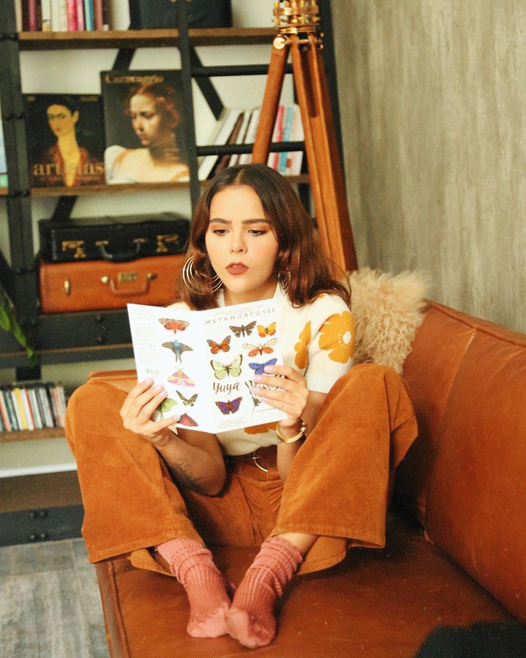 Foto de Yuya en un sillón con la paleta de sombras Metamorfosis.