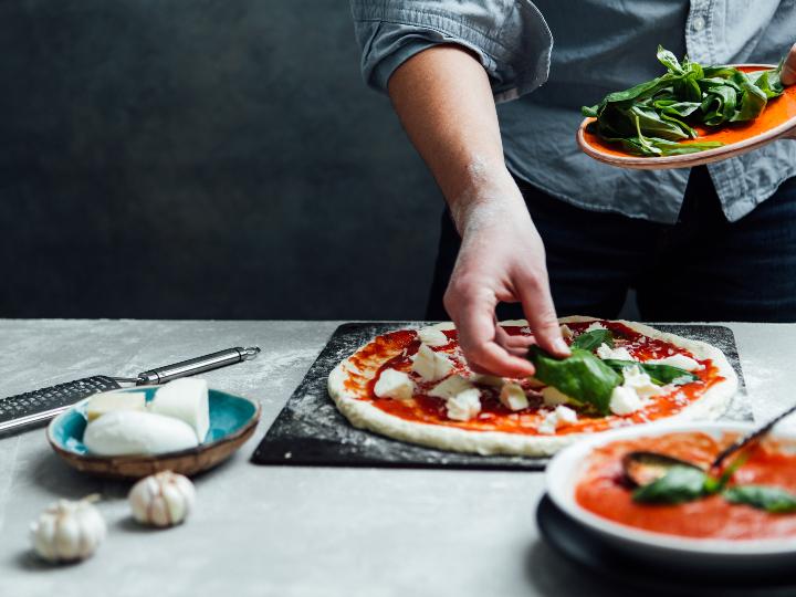 Las manos de un hombre ponen sobre la masa de la pizza los ingredientes que la van a acompañar.