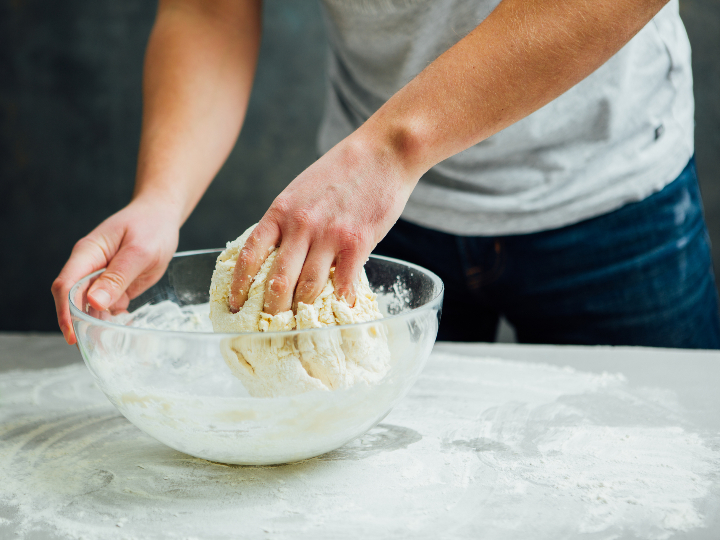 Las manos de un hombre amasan los ingredientes, dentro de un bowl, para  elaborar una pizza.