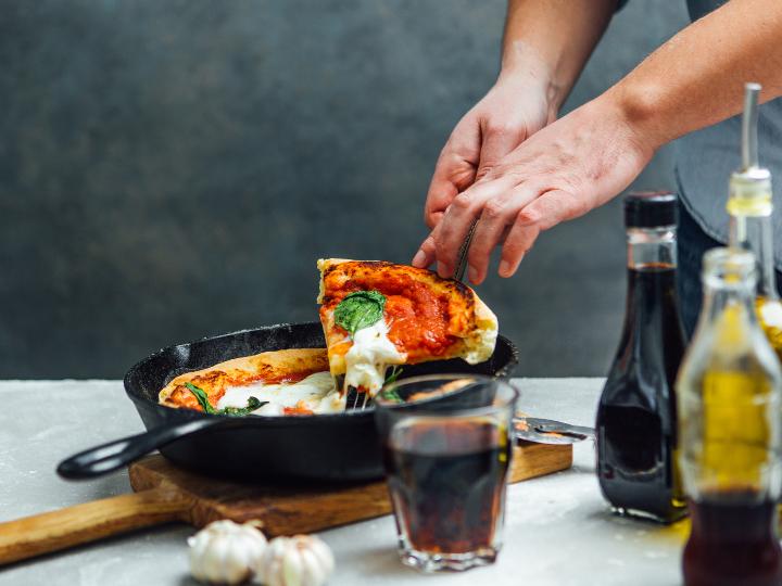 Las manos de un hombre sujetan una rebanada de pizza de sartén.