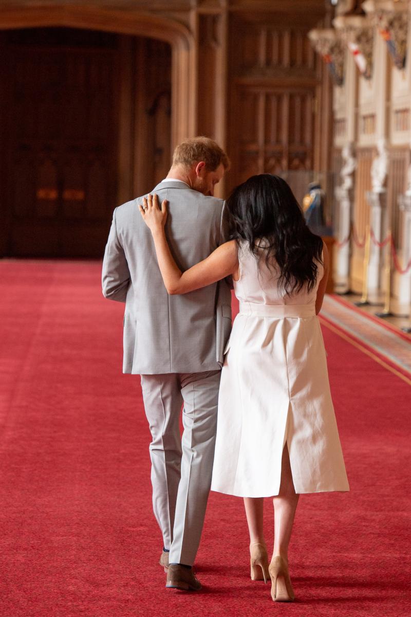El príncipe Harry y Meghan caminan de espaldas para irse, mientras cargan a su bebé.