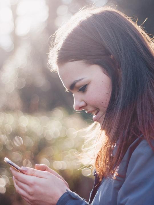 imagen ilustrativa: mujer sostiene un smartphone y sonríe.