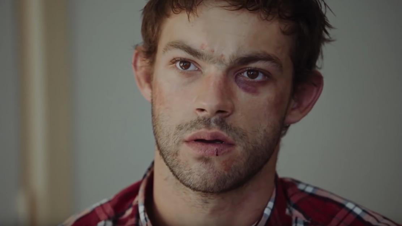 Leo el protagonista de Sauvage aparece en primer plano con una camisa a cuadros color roja.