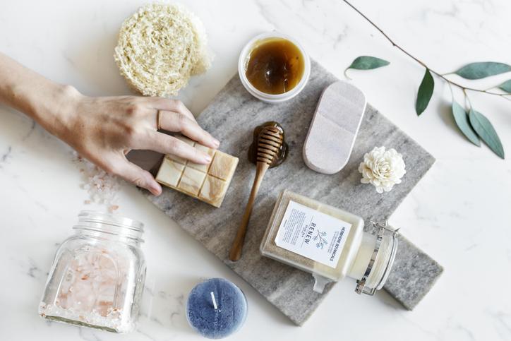 Productos de cuidado facial y de la piel sobre un trozo de mármol: sales, miel, jabón e instrumentos para el cuidado de la piel.