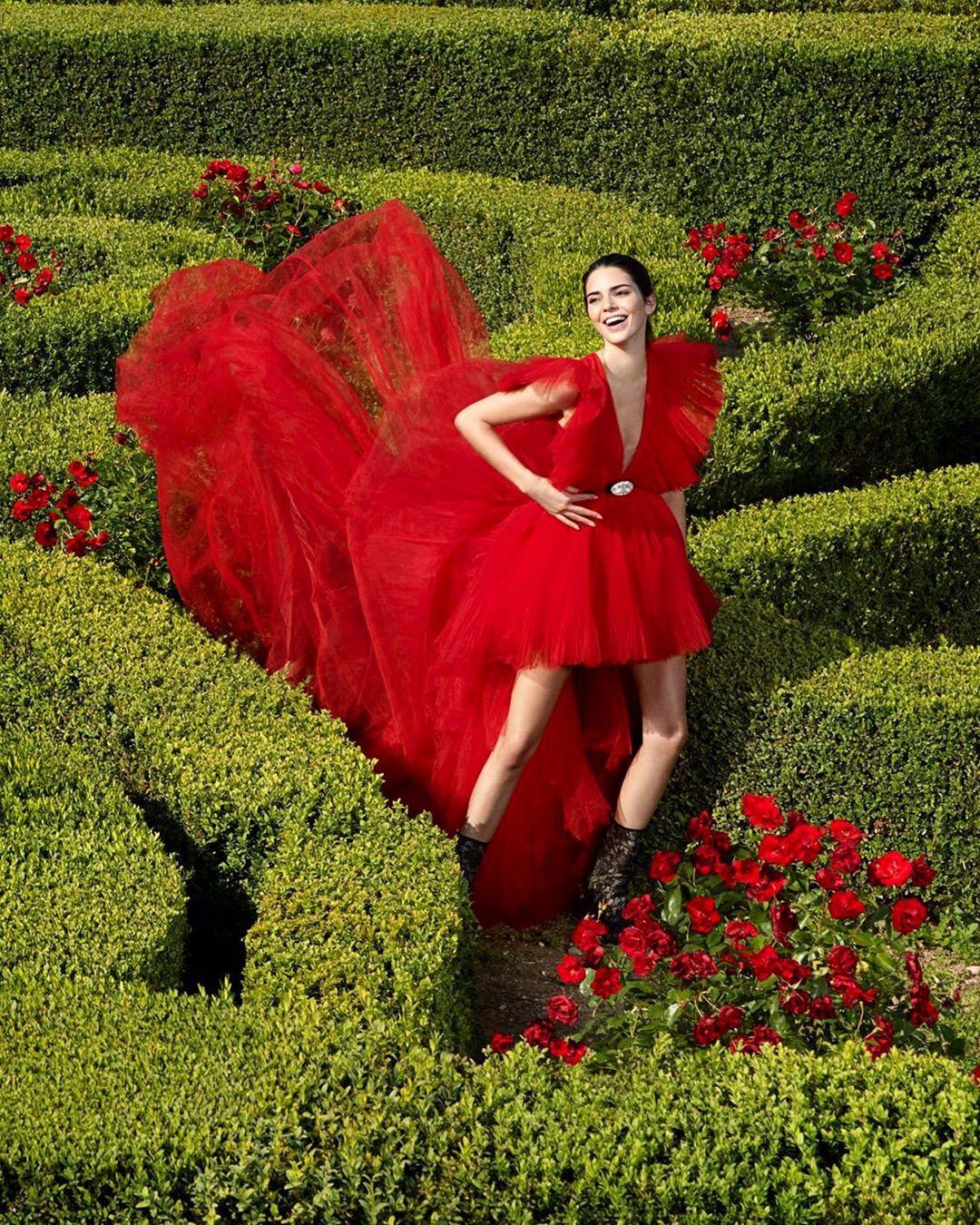 Kendall Jenner en un jardín con flores rojas, luciendo el vestido de Giambattista Valli en colaboración con H&M.